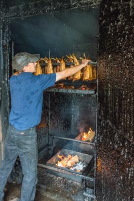 Chris removing racks of smoked salmon from the smokehouse. Photo by Len Villano.