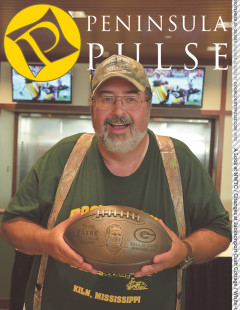 Pete D'amico holds up Brett Favre's bronze football commemorating the former quarterback's induction into the Green Back Packers' Hall of Fame in July. Submitted photo