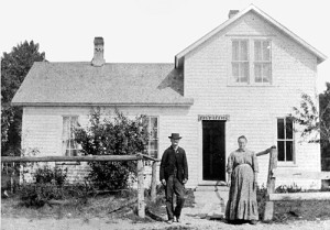 """Andrew Hanson and his wife are shown in front of their house along Ephraim's """"lower road."""" Hanson was appointed postmaster in 1894 and served for 21 years, operating the post office out of his home (a sign over the door says """"Post Office""""). The house still stands along Hwy 42 in downtown Ephraim. Photo courtesy of the Ephraim Historical Foundation collection."""