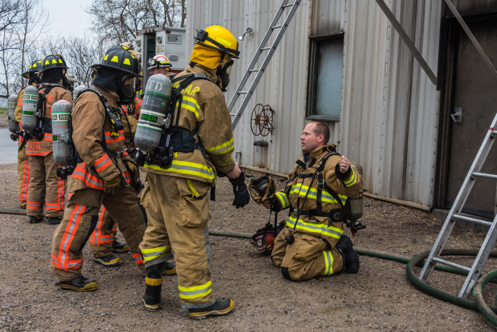 Gibraltar Fire Chief Jerrad Anderson (kneeling) talks to recruits during training at the NWTC-Green Bay burn tower. Photo by Len Villano.