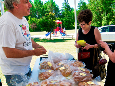 Customers meet the artisan and sample cheesecake at the Jacksonport Farmers Market. Photo by Len Villano.