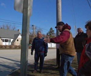 Jacksonport Plan Commission member Tim Bley does a quick arm measurement of the intersection when the Plan Commission used part of its April 11 meeting to walk the area of the walking paths the town plans to install for this season. Photo by Jim Lundstrom.