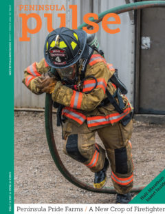 Sister Bay/Liberty Grove recruit Mitch Olson puts his back into moving a charged hose during training at the NWTC-Green Bay burn tower. Photo by Len Villano.