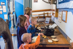Children try their hand at an old typewriter in one of the museum's interactive displays. Photo by Len Villano.