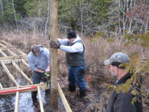 The Peil Construction crew gets knee deep in cold spring water while installing The Ridges new boardwalk. Photo by Ed Miller.