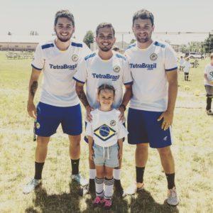 Brazilian soccer coaches Kaio Lamounier, Iago Boaventura, and Mauricio Santos stand with Delaney Skiba during the TetraBrazil Soccer camp.