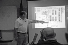 Tom Ash, Jacksonport's fire chief and chair of the town's Buildings & Grounds Committee, shows the floor plans for the proposed renovation and expansion of the town hall and fire station during a public presentation on Oct. 20. The committee will hold another public review of the plans at 10 am on Oct. 1. Photo by Jim Lundstrom.