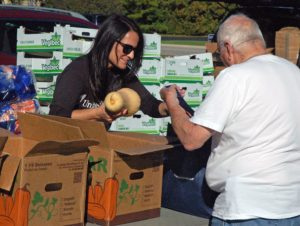United Healthcare employee Brenda Leich places a butternut squash in Ron LeSech's bag, who was picking up food for his housebound Aunt Pat.