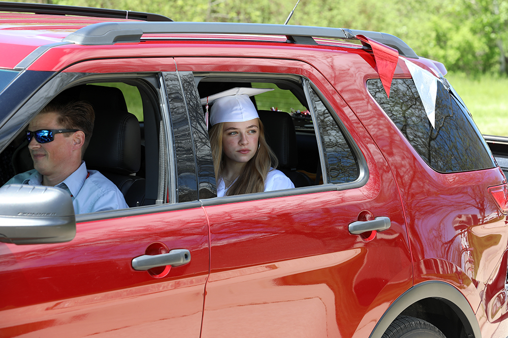 Kasia Klotz, 18, is seen in her car during the processional at the Sturgeon Bay High School graduation ceremony on Sat. May 30, 2020.  High school graduations had a much different look in 2020. At Sturgeon Bay High School, students received their diplomas during a drive-up ceremony at the school's front doors. Photo by Coburn Dukehart.