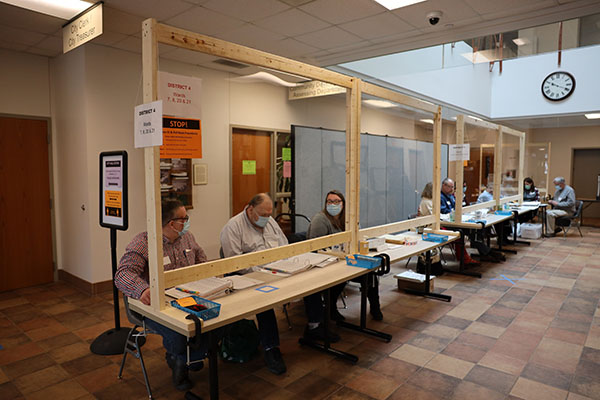 Poll workers sit behind newly built sneeze guards, provided by municipal services, at the polling location at Sturgeon Bay City Hall in Sturgeon Bay, Wis., during the Wisconsin primary election on April 7, 2020.