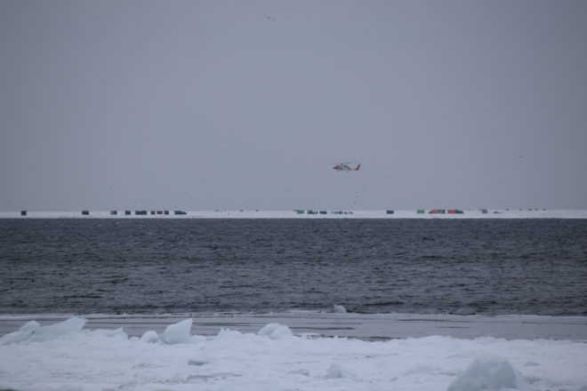 A U.S. Coast Guard helicopter with people awaiting rescue on an ice floe can be seen from shore just north of Little Harbor. Photo by Doug Henderson.